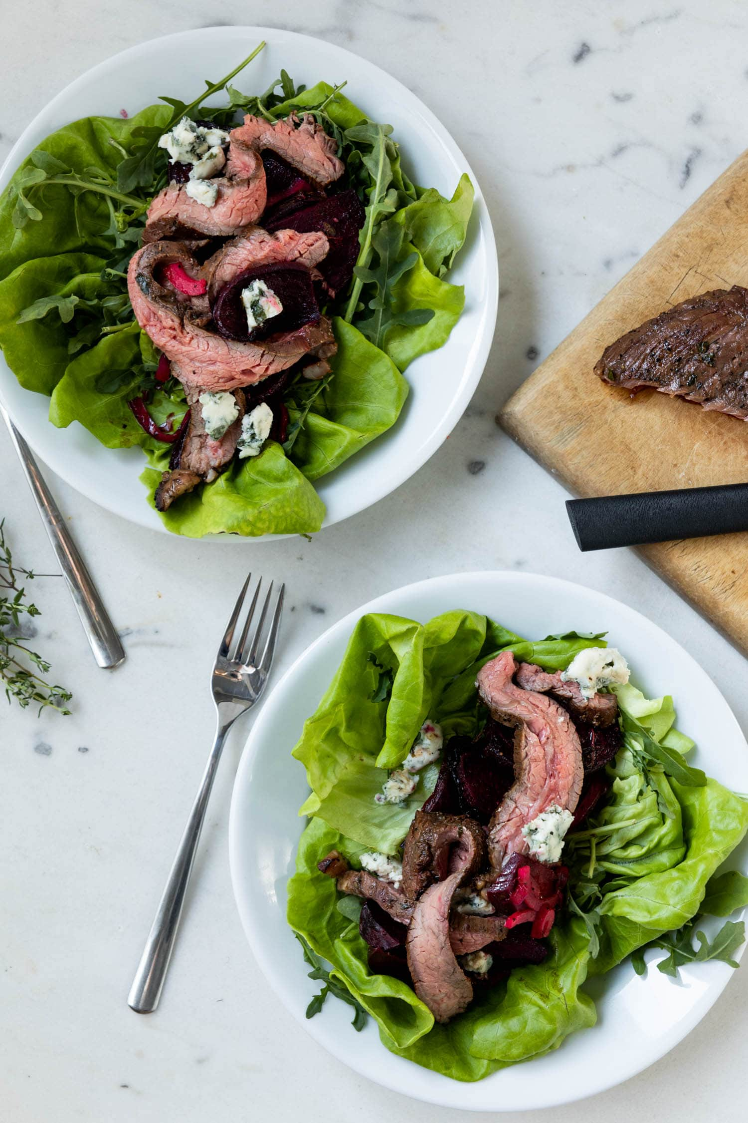 Butter lettuce and arugula topped with grilled flank steak, grilled beets and feta on two white plates with steak, cutting board and knife on a marble surface.